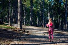 年轻人在佩带巧妙的手表和拿着瑜伽席子的森林里适合了运动妇女,轻易地胜过照相机 库存图片