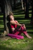 年轻人在佩带巧妙的手表的森林里适合了运动妇女坐地面在瑜伽席子旁边 身心概念 库存照片