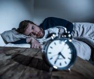 年轻人在充满绝望闹钟不能的感觉和的困厄的床上睡觉以失眠 免版税库存图片