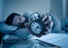 年轻人在充满绝望闹钟不能的感觉和的困厄的床上睡觉以失眠 免版税图库摄影