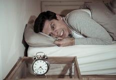 年轻人在充满绝望闹钟不能的感觉和的困厄的床上睡觉以失眠 免版税库存照片