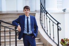 年轻人在公园今天结婚,他佩带了经典蓝色衣服、衬衣和领带,步行,在附近的姿势 图库摄影