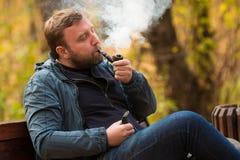 年轻人在公园抽烟斗 库存照片