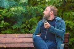 年轻人在公园抽烟斗 免版税图库摄影