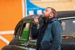 年轻人在减速火箭的汽车旁边抽烟斗 免版税库存图片