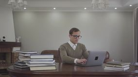 年轻人在办公室谨慎地打扮了坐在木桌上的玻璃的人,许多书在桌上 ?? 股票录像