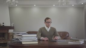 年轻人在办公室,许多书谨慎地打扮了坐在木桌上的玻璃的人,并且膝上型计算机在桌上 影视素材