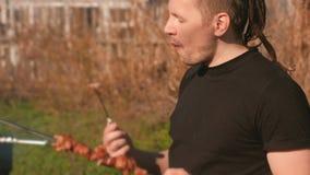 年轻人在后院在春天吃着肉在串的shashlik烤肉有刀子的在一个晴天 股票录像