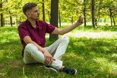 年轻人在夏天p拍与智能手机的selfie照片 免版税库存照片