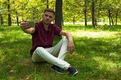 年轻人在夏天p拍与智能手机的selfie照片 库存图片