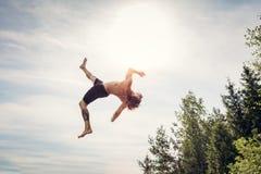年轻人在天空中的做一backflip 免版税库存照片