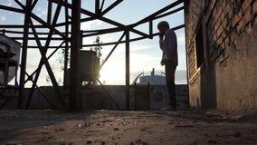 年轻人在建造场所站立并且在slo mo叫 股票视频