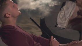 年轻人在扶手椅子坐在水烟筒旁边 影视素材