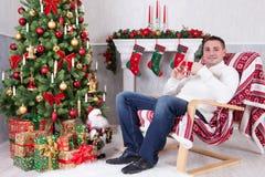 年轻人在扶手椅子坐并且在与xmas礼物的圣诞树附近拿着杯子 与圣诞节长袜的一个壁炉在backgroun 免版税库存照片