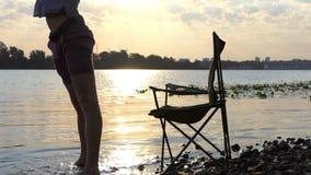 年轻人在折叠椅在河岸的水中坐,站起来,移动 股票录像