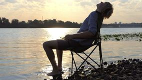 年轻人在折叠椅站立并且下来坐河岸在Slo Mo 影视素材