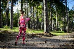 年轻人在拿着桃红色瑜伽席子的森林里适合了运动妇女,轻易地胜过照相机 图库摄影