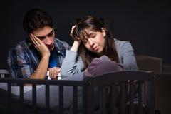 年轻人在晚上做父母失眠与新出生的婴孩 免版税库存图片