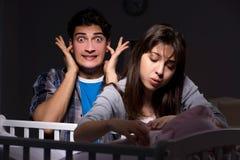 年轻人在晚上做父母失眠与新出生的婴孩 库存照片