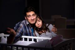 年轻人在晚上做父母失眠与新出生的婴孩 免版税库存照片
