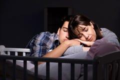 年轻人在晚上做父母失眠与新出生的婴孩 免版税图库摄影