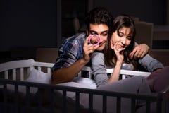 年轻人在晚上做父母失眠与新出生的婴孩 库存图片