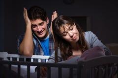 年轻人在晚上做父母失眠与新出生的婴孩 图库摄影