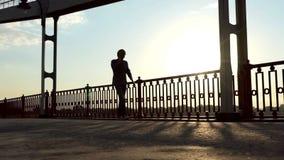 年轻人在有智能手机的一座桥梁走手头在慢动作的日落 股票视频