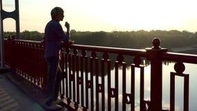 年轻人在桥梁看Dnipro河,微笑并且认为 股票视频