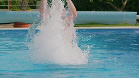 年轻人在水池的飞溅水 影视素材