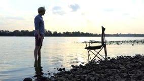 年轻人在河岸和Keedps的水中赤足站立一块石头在Slo Mo 股票视频