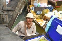 年轻人在浮动市场芭达亚泰国上的卖椰子 免版税库存照片