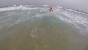 年轻人在海洋学会游泳在一个冲浪板 股票录像