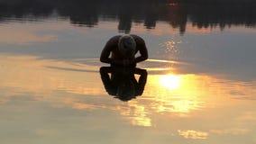 年轻人在湖水域中站立,祈祷和弯,在精采日落 股票视频