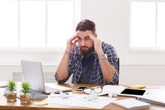 年轻人在现代白色办公室注重了与膝上型计算机的商人 库存图片
