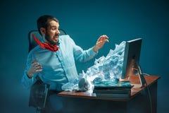 年轻人在现代的办公室注重了工作在书桌的英俊的商人呼喊在膝上型计算机屏幕和恼怒 库存照片