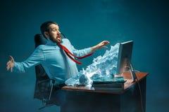 年轻人在现代的办公室注重了工作在书桌的英俊的商人呼喊在膝上型计算机屏幕和恼怒 图库摄影