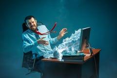 年轻人在现代的办公室注重了工作在书桌的英俊的商人呼喊在膝上型计算机屏幕和恼怒 免版税库存图片