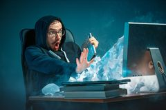 年轻人在现代的办公室注重了工作在书桌的英俊的商人呼喊在膝上型计算机屏幕和恼怒 免版税库存照片