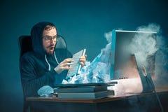 年轻人在现代的办公室注重了工作在书桌的英俊的商人呼喊在膝上型计算机屏幕和恼怒 免版税图库摄影