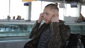 年轻人在耳机投入,当坐在机场时 股票视频