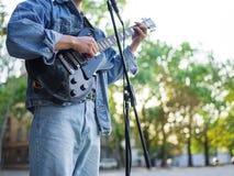 年轻人在自然本底的一个公园唱歌曲并且弹在一件牛仔裤夹克的吉他 免版税图库摄影
