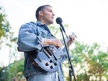 年轻人在自然本底的一个公园唱歌曲并且弹在一件牛仔裤夹克的吉他 库存图片