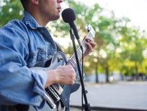 年轻人在自然本底的一个公园唱歌曲并且弹在一件牛仔裤夹克的吉他 库存照片