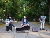 年轻人在自然本底的一个公园唱歌曲并且弹在一件牛仔裤夹克的吉他 免版税库存图片