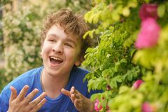 年轻人在花中站立并且享受夏天和开花 免版税图库摄影