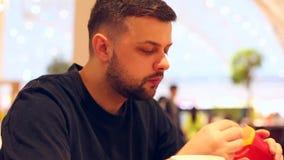 年轻人在餐馆享用一个可口汉堡和薯条 股票录像