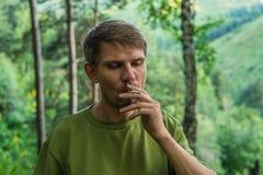 年轻人在mounta的一个夏天森林里抽香烟 免版税库存照片