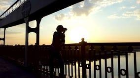 年轻人在Slo Mo放松,喝咖啡并且享受在一座桥梁的日落 股票视频