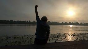 年轻人在Slo Mo时举他的拳头,当坐河岸在日落 股票视频